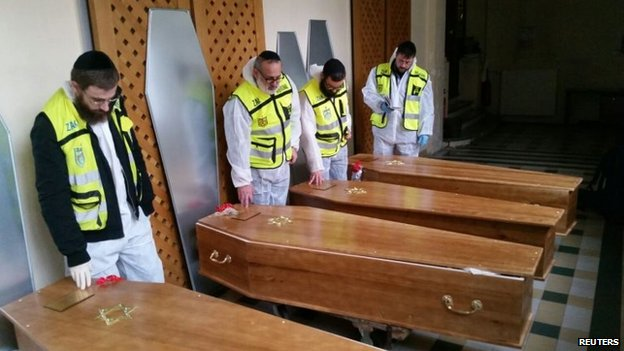Members of the Zaka emergency response team pray beside the coffins of four victims of an attack at a kosher supermarket on Friday, before their transport from Paris to Israel for burial, 12 January 2015