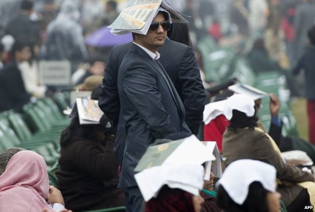 An Indian spectator tries to protect himself from the rain as he attends the Republic Day Parade
