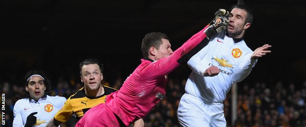 Robin Van Persie is hit in the face by Cambridge goalkeeper Chris Dunn