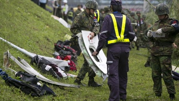 A rescue crew carries a window from a TransAsia Airways ATR 72-600 turboprop airplane that crashed into the Keelung River shortly after takeoff from Taipei Songshan airport on February 4, 2015 in Taipei, Taiwan