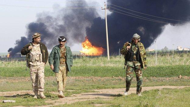 Smoke and flames behind Kurdish peshmerga forces, on the outskirts of Kirkuk