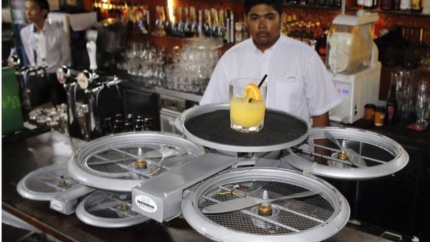A bartender watches as an Infinium-Serve Flying Robot takes off with an order at a restaurant during a pilot demonstration for the media in Singapore 5 February 2015