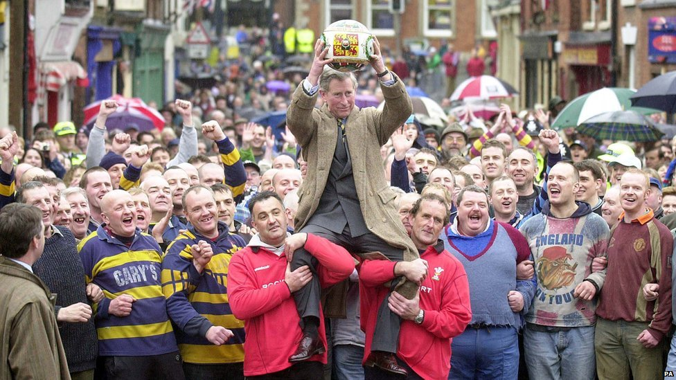 Prince Charles being lifted up holding the ceremonial ball before starting the ancient Royal Shrovetide Football game, in Ashbourne, Derbyshire. Holding the Prince shoulder-high were Dougie Souter and Mark Harrison (right of Prince with dark hair).