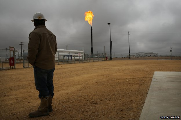 Texan oil worker contemplates flare from well