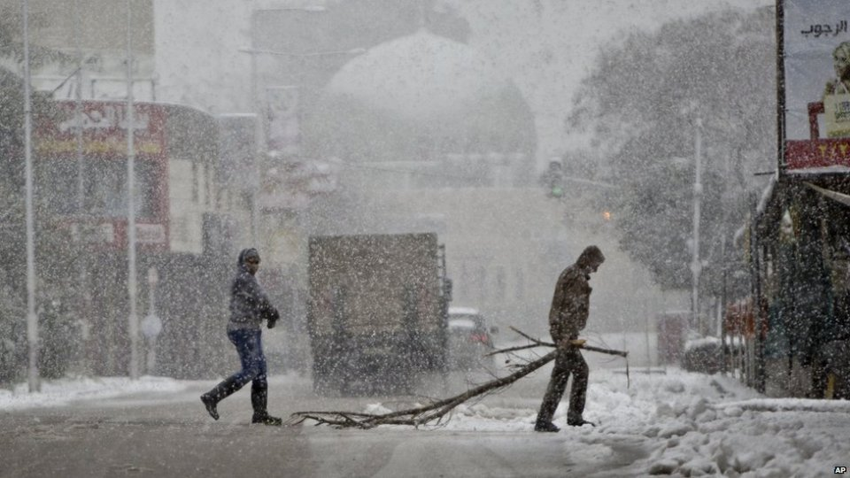 Palestinians cross a snow-blanketed street in the West Bank City of Nablus, Friday, Feb. 20, 2015