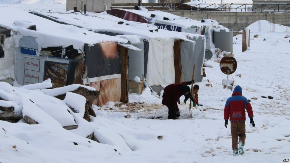 Syrian refugees walk in a makeshift camp covered in snow on February 20, 2015 on the outskirts of the Lebanese town of Baalbek
