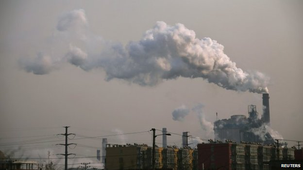 Smoke rises from a chimney of a steel plant next to residential buildings on a hazy day in Fengnan district of Tangshan, Hebei province in this 18 February 2014 file picture