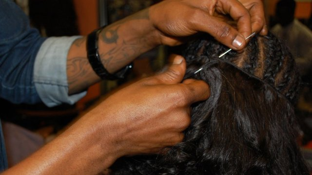 A hairdresser sewing on a weave at Bruno's Place hair salon in Ikeja Mall in Lagos, Nigeria