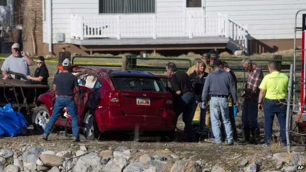 In this March 7, 2015 photo, officials respond to a report of car in the Spanish Fork River near the Main Street and the Arrowhead Trail Road junction in Spanish Fork, Utah