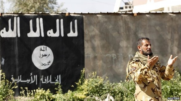 Shia militiaman from the Popular Mobilisation prays in al-Alam, beside a wall painted with Islamic State's flag (11 March 2015)