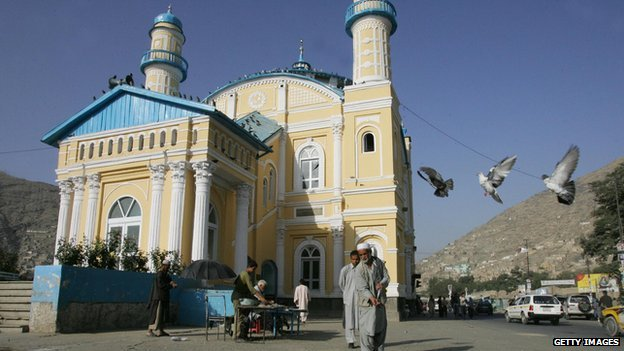 Afghan men feed pigeons in front of the Shah-Du-Shamshaira mosque, in Kabul, 11 September 2005
