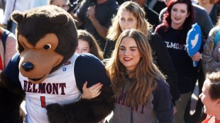 JoJo linking arms with Belmont's mascot in a crowd of students