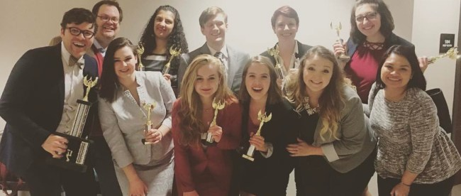 Students and their coaches pose after winning the national championship for individual events at a forensics competition.