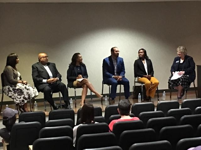 The panel presents to a group of faculty, staff and students.