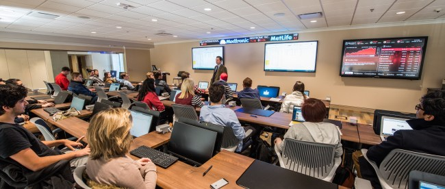 Students in the financial trading room listen to a professor.