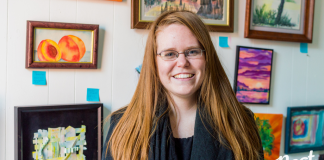 Alumna Nicole Brandt stands in front of her artists' work at Poverty and the Arts, a nonprofit she founded after graduating from Belmont University