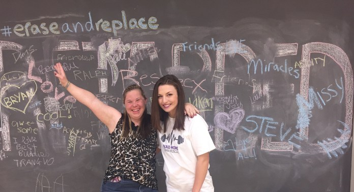 A Belmont student (right) poses with her community buddy (left) in front of a chalkboard that has been decorated.
