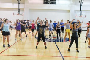 Students doing jumping jacks in the rec center gym