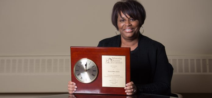 Dr. West and her award from Minority Access, Inc.