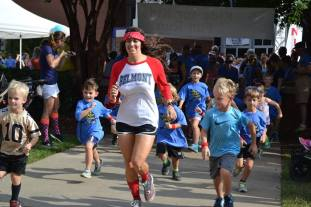 A Belmont DPT student runs alongside children who are participating in the Fun Run.