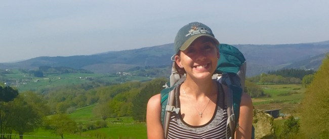 Erin Sanislo, carrying hiking backpack, with rolling hills behind her