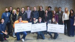 Students holding large checks