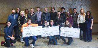 Students holding large checks