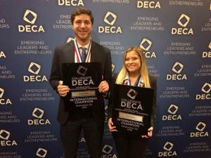 two students posing with winners plaque