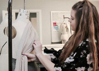 student pinning fabric to a dress form