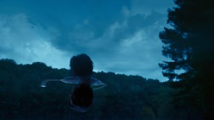 "A still image for the film ""A Sacred Disease"" shows a person standing in front of a sunset sky."