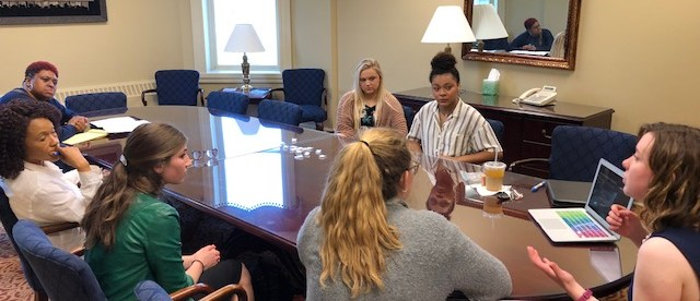 students presenting work to Easley representatives, sitting at a conference table