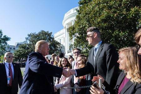 Riggs is greeted by President Donald J. Trump as he walks across the South Lawn of the White House to meet the White House interns Thursday, Oct. 18, 2018, prior to boarding Marine One to begin his trip to Montana, Arizona and Nevada. (Official White House Photo by Joyce N. Boghosian)