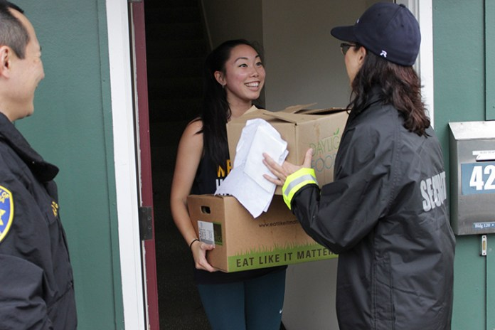 Sam, a UC Berkeley optometry student who didn't want to give her last name, accepts her turkey dinner from Terri Castenade, a civilian police administrator, while police Captain Alex Yao watches. (UC Berkeley photo by Jeremy Snowden).