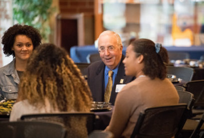 Bob Haas sitting at a table with students