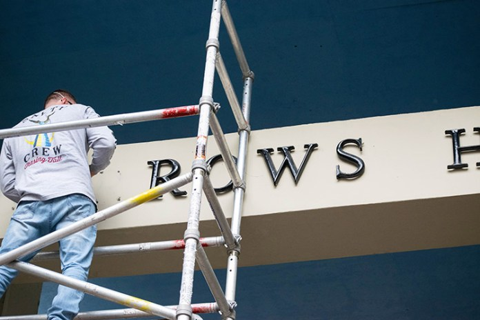 A worker stands on scaffolding to remove metal letters from the exterior of Barrows Hall.