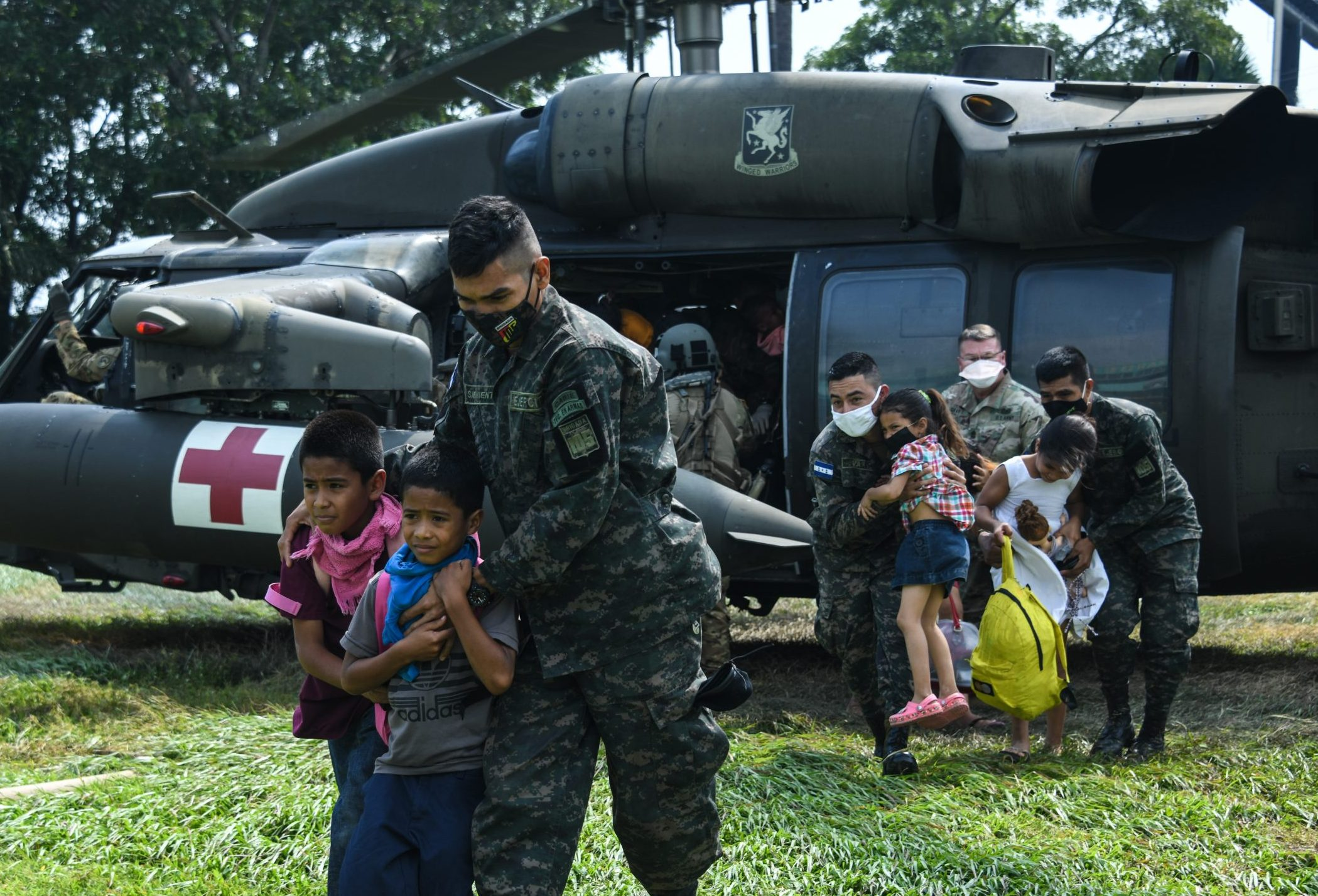 Joint Task Force-Bravo members and Honduran soldiers escort rescued Honduran family off of U.S. Army HH-60 Black Hawk helicopter at San Pedro Sula, Honduras, Nov. 13, 2020. JTF-Bravo's forward deployment to Honduras highlights the importance of cooperation and training with partners to build trust and teamwork. (U.S. Air Force photo by Staff Sgt. Elijaih Tiggs) (Photo Credit: Staff Sgt. Elijaih Tiggs)