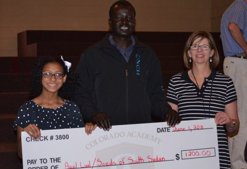 Kendall Cooper, Middle School student, and Sue Counterman present the check to support Aguil to Arok.