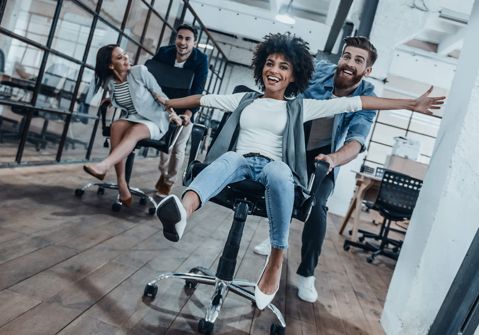 employees playing in office on chairs