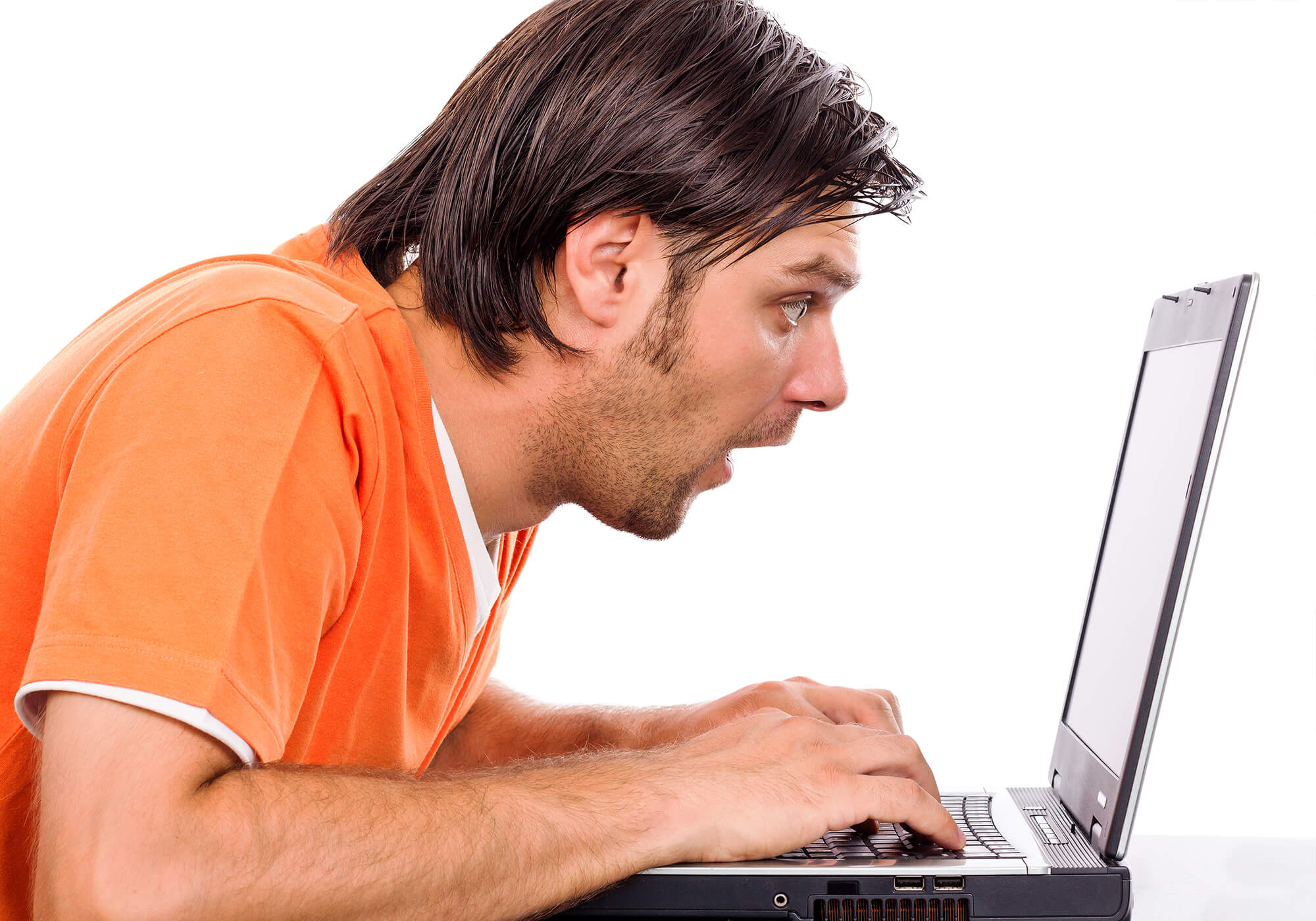man in orange shirt looking at laptop screen in shock