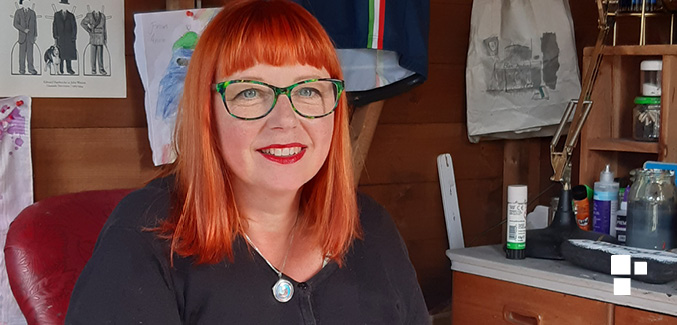 Photo of Karen who has red hair and is wearing glasses with a green frame.