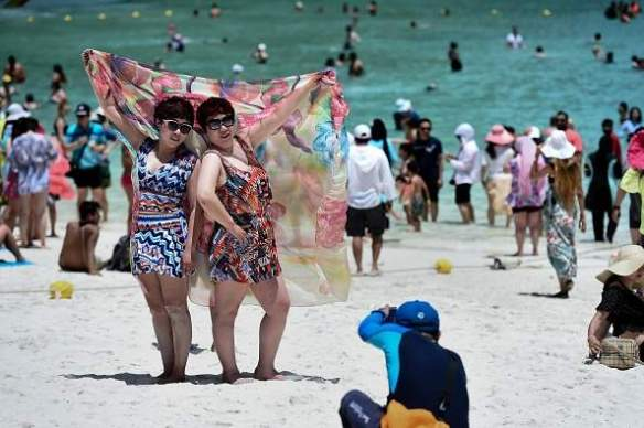 Tourists having their photo taken by a guide on Maya Bay before its closure