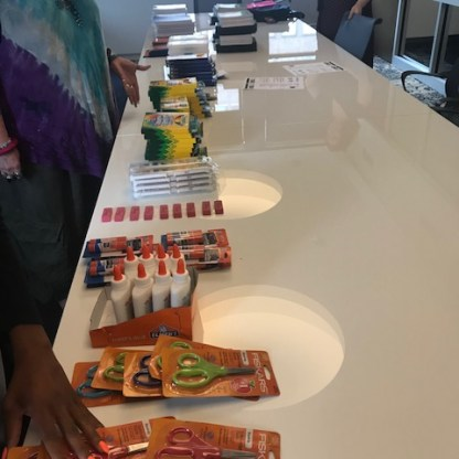 table with school supplies to fill backpacks for Operation Backpack
