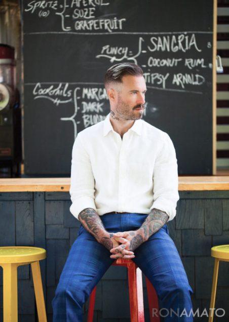 Gabe LaDuke sitting on a stool in front of a chalkboard