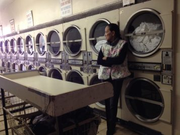 still from The Washing Society with woman in front of rows of commercial washers
