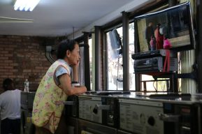 still from The Washing Society with woman watching TV at the laundromat