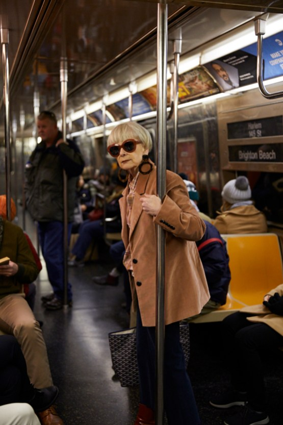 Grey haired woman with large sunglasses and tan leather jacket riding a NYC subway car