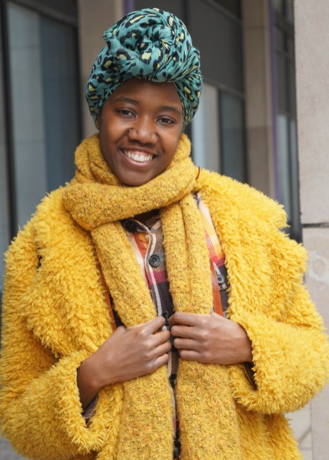 Young african american woman with teal leopard rpint head wrap and mustard yellow coat