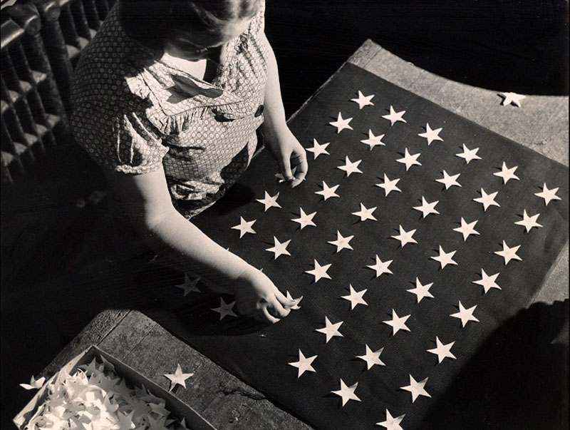 An employee embroiders stars by hand circa 1930.