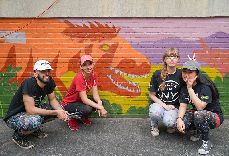 one man, two woman, crouch in front of mural of dinosuar