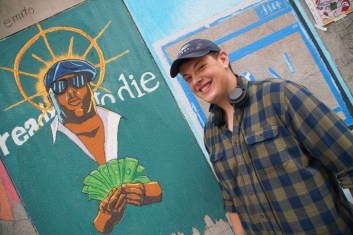young man smiling in front of mural of rapper Christopher Wallace aka Notorious B.I.G